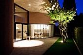 Grosszügige, gepflasterte Terrasse vor zeitgenössischem Wohnhaus mit gebogener Glasfassade, in Abendbeleuchtung