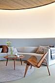 Klassikerstuhl und Coffeetable aus Holz auf rundem Teppich, vor hellgrauem, massgefertigtem Sofa an gebogener Wand