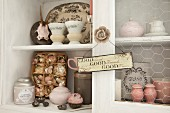 Pastel vintage china and shabby-chic knick-knacks in white dresser with motto on sign hung from rose-shaped handle