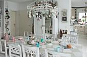 Mit Anhängern dekorierte Pendelleuchte über Tisch mit Schachbrettmuster und Sammlung weiss lackierter Holzstühle
