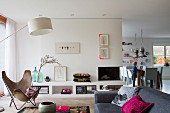 Butterfly chair, standard lamp and low masonry sideboard in open-plan interior