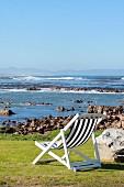 Liegestuhl an der Küste mit Blick aufs Meer