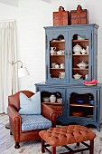 Vintage crockery in blue vintage dresser, brown leather armchair and Chesterfield footstool