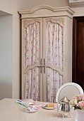 Old wardrobe with curtains behind glass doors
