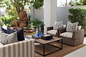 Outdoor seating area with coffee table, wicker armchairs, sofa and decorative terracotta pots in background