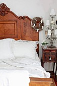 Antique wooden bed and bedside cabinet with carved ornamentation