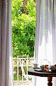 View across breakfast table though wafting curtains into green garden