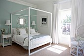Modern four-poster bed in white and pastel turquoise bedroom