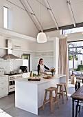 Junge Frau kocht in weißer, offener Küche mit Kücheninsel, offenem Dach und Sichtbalken