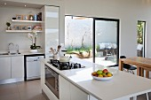 White open-plan kitchen with island counter and open terrace doors