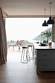 View past two bar stools at kitchen counter to lounger on terrace