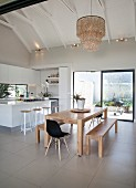 Open-plan kitchen-dining area with island counter and wooden table below exposed beams in open roof area