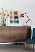 Industrial-style table lamp and artwork with graphic motif on retro sideboard with dark front wooden