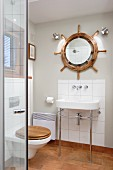 Washstand with metal frame against small tiled splashback below mirror in centre of ship's wheel on wall of modern bathroom