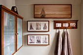 Framed photos of sailing ships and towels hanging from wall hooks; wooden wall cabinet with opaque glass doors to one side