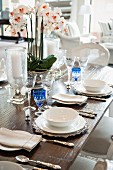 Detail of table set with crystal glasses, white crockery, silver cutlery and orchid