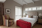 Classic bedroom with exposed ceiling beams, ottoman at foot of bed and striped armchair