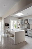 Plexiglas bar stools and island counter in open-plan modern kitchen in shades of grey