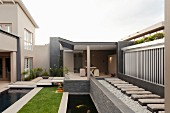 Modern designer garden with linear configuration of pool, lawn, pond and seating area
