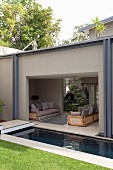 View into roofed seating area with sofas behind lawn and pool