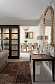 View past Illuminated display case and mini-bar into classic dining room