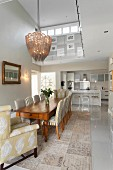 Classic dining room in shades of green and grey with elegant upholstered chairs and view into open-plan kitchen