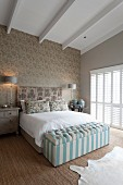 Elegant double bed with ottoman at foot in classic bedroom with exposed ceiling beams
