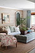 Pastel living room with wicker sofa against wooden wall, velvet ottoman, floral armchair and jute rug