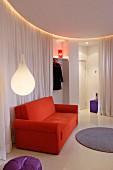 Tropfenförmige Hängeleuchte und orangerotes Sofa vor weißem Vorhang als Raumabtrennung in minimalistischem, kreisförmigem Loungebereich