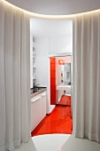 View through open curtain into modern kitchenette with orange floor and view into bathroom through open sliding door