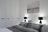 Double bed with grey patterned bed linen and black table lamps on headboard shelf in modern bedroom with white fitted wardrobes