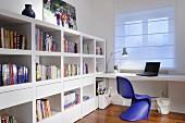 Violettblauer Retro Schalenstuhl aus Kunststoff vor Schreibtisch am Fenster mit heruntergelassenem Rollo, seitlich weisses Bücher-Regal mit Schubladen Elementen
