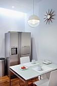 Esstisch mit Frühstücksgedecken unter Kugelhängeleuchte, in Zimmerecke Edelstahl Kühlschrankkombination