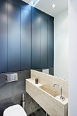 Stone, trough-style sink on mirrored wall and fitted cupboards with black doors in designer bathroom