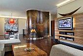Integrated interior design in open-plan living-dining room; matching wood structure on media wall and coffee table; fireplace in curved wall element in background