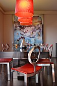 Orange lamps above dark, exotic wood table and metal chairs with circular backrests; surreal artwork in background