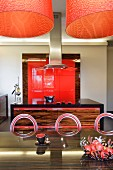 Orange lamps above dark exotic wood table and metal chairs with circular backrests in open-plan exotic wood kitchen with red fitted elements