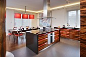 Cooker in island counter in open-plan kitchen with exotic wood fronts and red accents on handles; colour-coordinated dining area in background