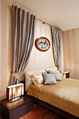 Bed with gold bed linen, striped wallpaper and draped curtains in elegant, traditional bedroom