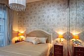 French bed with upholstered headboard and table lamps on bedside cabinets against wall with pale silk wallpaper in traditional bedroom