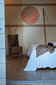 Blick von Aussen in ein Schlafzimmer auf Bett mit weisser Tagesdecke, im Hintergrund bemalte Wand