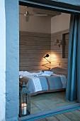 View through open terrace door into wood-clad bedroom with retro table lamp in corner