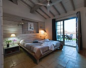 Double bed against wood-clad wall, table lamps on bedside cabinets and open terrace doors with a view in Mediterranean bedroom