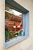 View of art collection and bicycle in interior seen through window with galvanised steel frame