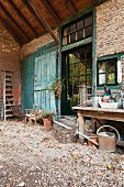 Gardening utensils on gravel floor in front of brick façade of old farmhouse with turquoise barn doors and industrial windows