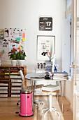 Weisser Tisch mit Bürostuhl und pinkfarbener Mülleimer in Zimmerecke