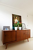 House plants and oil painting on top of fifties wooden sideboard