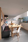 Comfortable kitchen-dining room with wooden table, upholstered bench and white Eames Chairs