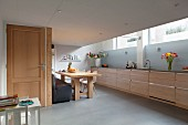 Elongated kitchen counter with pale wooden fronts and pale blue splashback in kitchen dining room with white children's table and kitchen door
