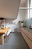 Elongated kitchen counter with pale wooden fronts in kitchen dining room with gallery